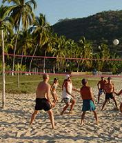 Tourists enjoying a game of beach volleyball at a beautiful beach